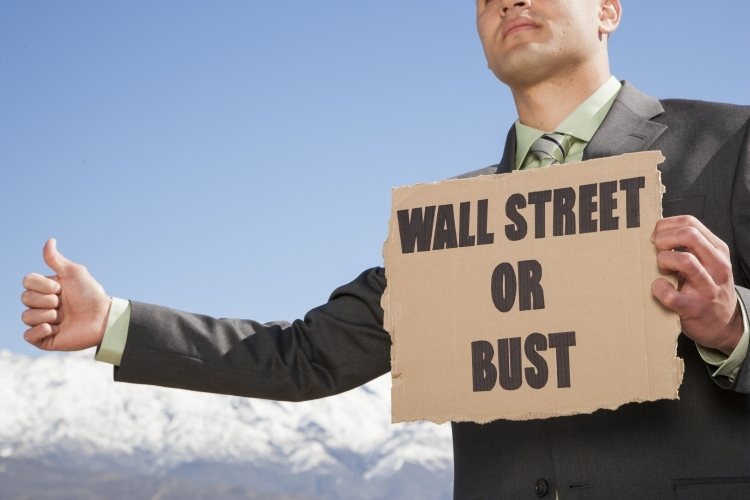 Man holding sign Wall Street or Bust